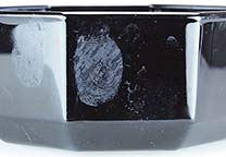 Fingerprints in blood on black glass object. Photographed with side lighting